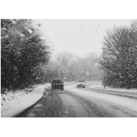 Two cars driving on a snowy road